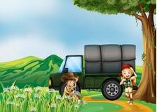 一个女孩和一个男孩在绿色卡车旁边 免版税库存图片