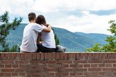 一个女孩和一个男孩爱的坐在大厦和容忍边缘 免版税库存图片