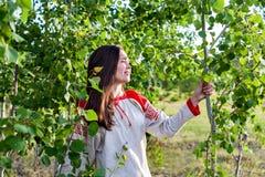 一个女孩和一个年轻森林的画象领域的在夏天 库存图片