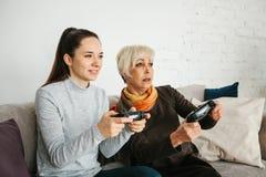 一个女孩和一名年长妇女在一个电子游戏一起打 联合消遣 家庭生活 通信  免版税库存照片
