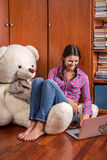 一个女孩和一头熊与膝上型计算机 免版税库存图片