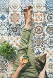 一个女孩和在床上的红色羊毛袜子的软的舒适照片温暖的毛线衣的与茶/咖啡在手上,顶视图 免版税库存照片