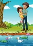 一个女孩和她的父亲河岸的 免版税库存图片