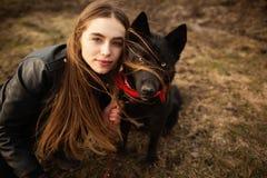 一个女孩和她的狗的一张美妙的画象与五颜六色的眼睛 朋友在湖的岸摆在 免版税库存图片