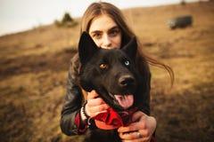 一个女孩和她的狗的一张美妙的画象与五颜六色的眼睛 朋友在湖的岸摆在 免版税图库摄影