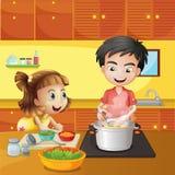 一个女孩和男孩厨房的 免版税库存图片