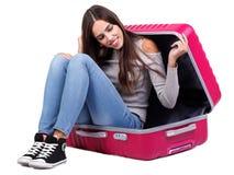 一个女孩在一个桃红色手提箱坐 背景查出的白色 库存照片