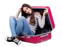 一个女孩在一个桃红色手提箱坐 背景查出的白色 免版税库存照片