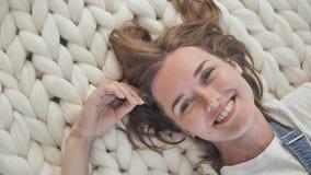 一个女孩在一条美利奴绵羊的白色毯子说谎在公园并且享受夏天天气 影视素材