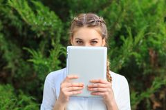 一个女孩在公园用片剂盖了她的面孔 免版税库存照片