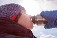 一个女孩在冬天穿衣热切地喝从瓶的水 免版税库存照片