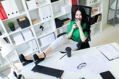 一个女孩在办公室在她的手上坐,投掷了她的在桌上的腿并且拿着电话 免版税库存图片