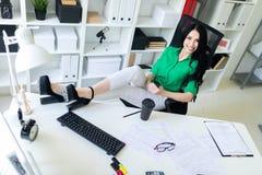 一个女孩在办公室在她的手上坐,投掷了她的在桌上的腿并且拿着电话 免版税库存照片
