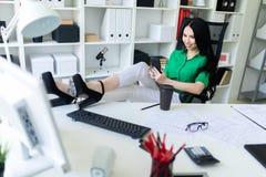 一个女孩在办公室在她的手上坐,投掷了她的在桌上的腿并且拿着电话 免版税图库摄影