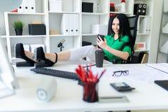 一个女孩在办公室在她的手上坐,投掷了她的在桌上的腿并且拿着电话 库存照片