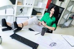 一个女孩在办公室在她的手上坐,投掷了她的在桌上的腿并且拿着电话 图库摄影