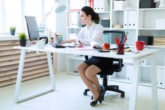 一个女孩在办公室在她的手上拿着一个桃红色标志并且与计算机和文件一起使用 图库摄影