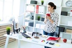 一个女孩在办公室在她的手上站立在桌附近,拿着一个红色杯子并且看显示器 库存照片