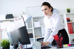 一个女孩在办公室在桌附近在她的手上站立,拿着一支铅笔和键入在计算机上的文本 免版税库存照片