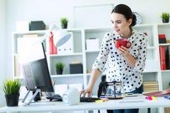 一个女孩在办公室在键盘在她的手上站立在桌附近,拿着一个红色杯子并且键入 免版税图库摄影
