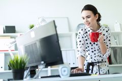 一个女孩在办公室在键盘在她的手上站立在桌附近,拿着一个红色杯子并且键入 图库摄影