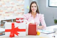一个女孩在办公室接受了许多礼物 免版税图库摄影