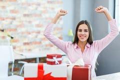 一个女孩在办公室接受了许多礼物 免版税库存图片