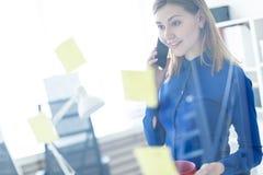 一个女孩在办公室站立在有贴纸的一个透明委员会附近,谈话在电话和拿着一个红色杯子  免版税图库摄影