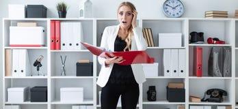 一个女孩在办公室站立在架子旁边并且拿着与文件的一个文件夹在她的手上 免版税库存照片