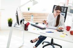 一个女孩在她的手、一个标志和计数上坐在一张桌上在办公室,拿着一支铅笔在计算器 免版税库存图片