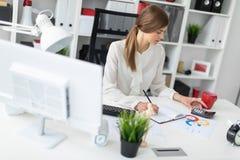 一个女孩在她的手上在一张桌上在办公室,拿着一支铅笔和计数坐计算器 免版税图库摄影