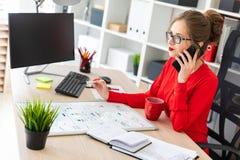 一个女孩在她的手上在书桌在办公室,拿着一个标志和谈话坐电话 在前面 免版税库存照片
