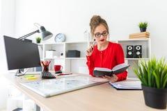 一个女孩在她的手上坐在一张桌上在办公室并且拿着一个黑标志 女孩与计算机,笔记薄一起使用 库存照片