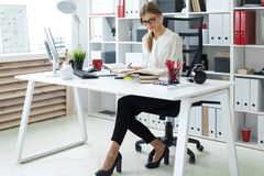 一个女孩在她的手上坐在一张桌上在办公室并且拿着一支铅笔 在女孩说谎开放前预定 免版税库存图片