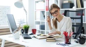 一个女孩在她的手上坐在一张桌上在办公室并且拿着一支铅笔 在女孩说谎开放前预定 库存图片