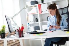 一个女孩在她的手上坐在一张桌上在办公室拿着一支铅笔并且调查本文 库存图片