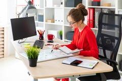 一个女孩在她的手上坐在一张桌上在办公室,拿着一个标志并且工作与笔记薄和一个磁性委员会 库存照片