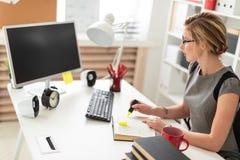 一个女孩在她的手上坐在一张桌上在办公室,拿着一个黄色标志 在女孩说谎开放前预定 免版税库存照片
