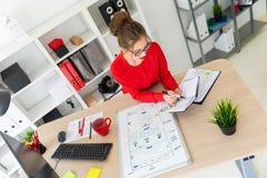 一个女孩在她的手上坐在书桌在办公室,拿着一个黑标志并且与笔记薄一起使用 A 免版税图库摄影