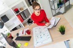 一个女孩在她的手上坐在书桌在办公室,拿着一个黑标志并且与笔记薄一起使用 A 免版税库存照片