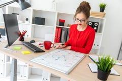 一个女孩在她的手上坐在书桌在办公室,拿着一个黑标志并且工作与一个磁性委员会 库存照片