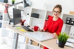 一个女孩在她的手上坐在书桌在办公室,拿着一个黑标志并且工作与一个磁性委员会 图库摄影