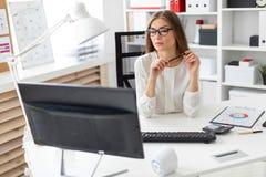 一个女孩在她的手上坐在书桌在办公室,拿着一支铅笔和看显示器 免版税库存照片