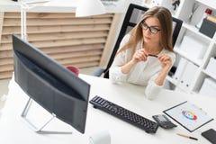 一个女孩在她的手上坐在书桌在办公室,拿着一支铅笔和看显示器 图库摄影