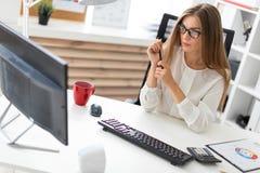 一个女孩在她的手上坐在书桌在办公室,拿着一支铅笔和看显示器 库存图片