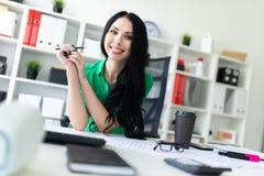 一个女孩在她的手上坐在办公室桌上并且拿着一支铅笔 免版税库存图片