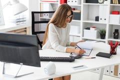 一个女孩在她的手上坐在计算机书桌在办公室,拿着一支铅笔和做在的笔记 免版税库存照片
