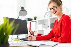 一个女孩在她的手上站立在一张桌上在办公室并且拿着一个黑标志 免版税库存照片