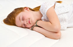 一个女孩在床上说谎 质量床垫 免版税库存图片