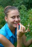 一个女孩在庭院里用在嘴的莓 库存照片